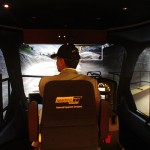 Minister Virk checks a side mirror while operating the haul-truck simulator.