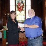 Jackie Brown accepts a cheque from Rev. Yme Woensdregt at Christ Church in Cranbrok on January 12.