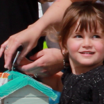 KRRG:child placing donation in KRRG box